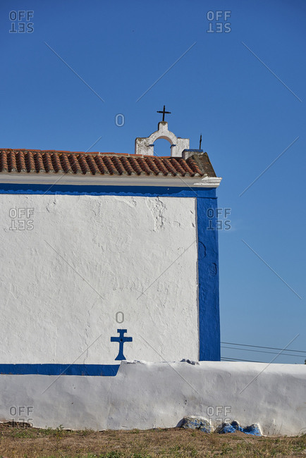 Whitewashed exterior wall of small church with blue painted cross in Sousel, Portugal