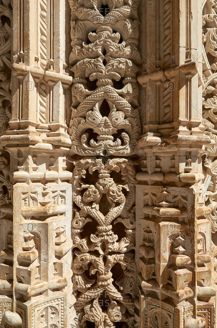 Sunlight highlighting complex carvings in pillar at Batalha Monastery in Portugal