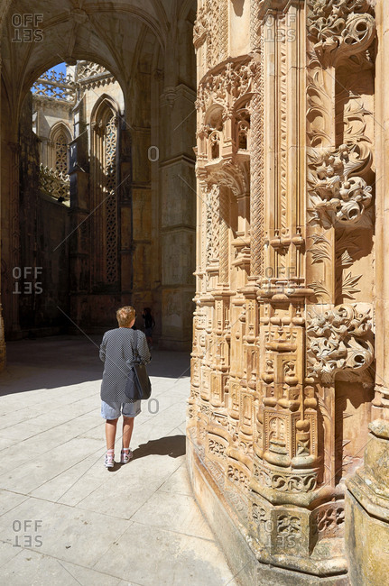 Tourist walking by ornate carvings in facade of Batalha Monastery in Portugal