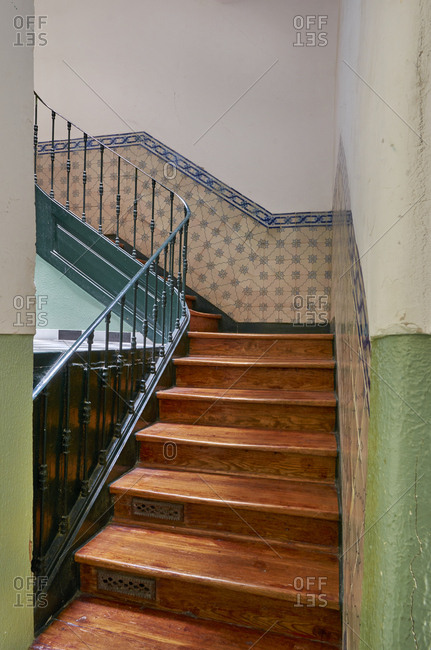 View of interior staircase with half tiled walls in walk up apartment in Lisbon, Portugal