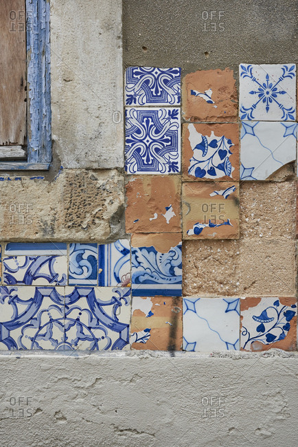 Cracked and mismatched flowered tiles on facade of building in Lisbon, Portugal