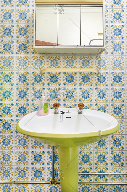 Bathroom interior with lime green pedestal sink and flowery tiles