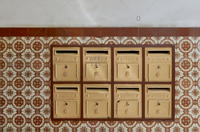 Residents mail boxes in lined up in half tiled wall in apartment building in Lisbon, Portugal