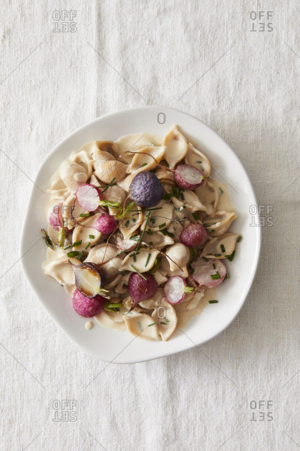 Whole wheat pasta shells with tahini, radishes and chives