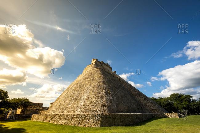Uxmal, Yucatan, Mexico - October 13, 2017: The Pyramid of the Magician (Piramide del Mago) towering in the Maya City of Uxmal, Mexico