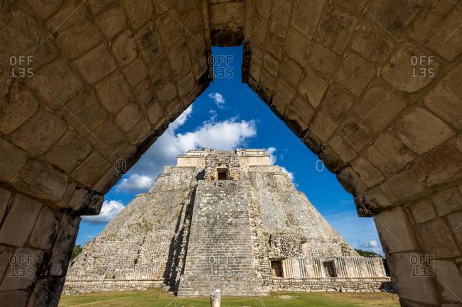 Uxmal, Yucatan, Mexico - October 13, 2017: View of the Pyramid of the Magician towering in the Maya City of Uxmal, Mexico