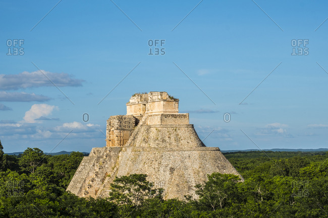 Uxmal, Yucatan, Mexico - October 13, 2017: The Pyramid of the Magician under blue cloudy skies in the Maya City of Uxmal, Mexico