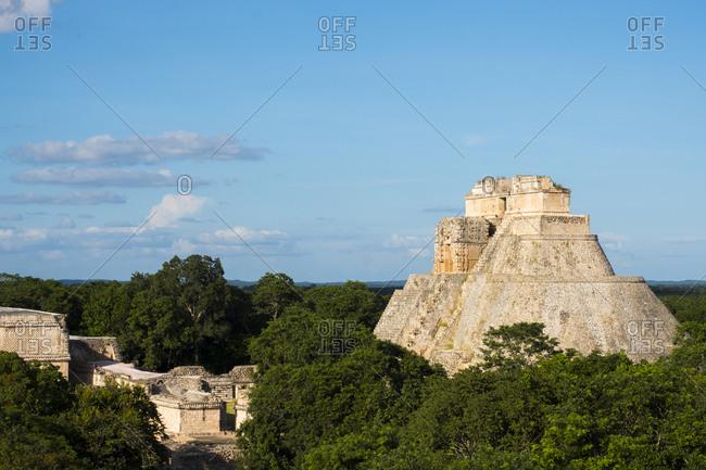 Uxmal, Yucatan, Mexico - October 13, 2017: Pyramid of the Magician under blue cloudy skies in the Maya City of Uxmal, Mexico