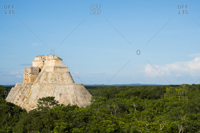 Uxmal, Yucatan, Mexico - October 13, 2017: The Pyramid of the Magician under blue cloudy skies in Uxmal, Mexico