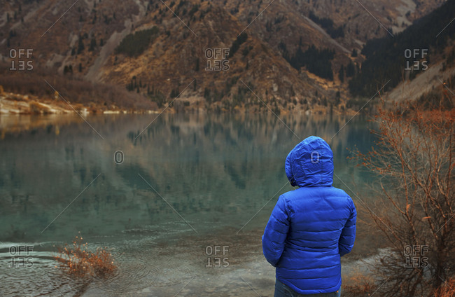 Woman in blue jacket with hood up at the mountain lake