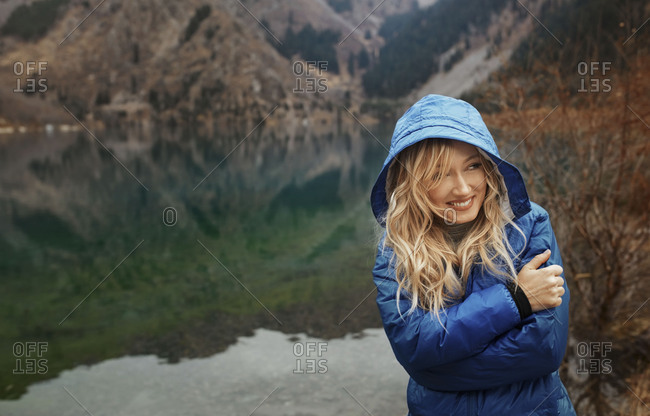 Smiling woman with hood up at the mountain lake