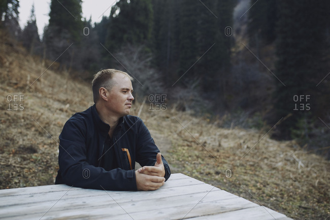 Adult man sitting at the picnic table in forest and mountain area