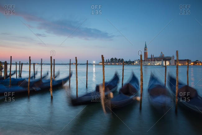 Long exposure of blue gondolas at dawn with the church of San Giorgio Maggiore in the background
