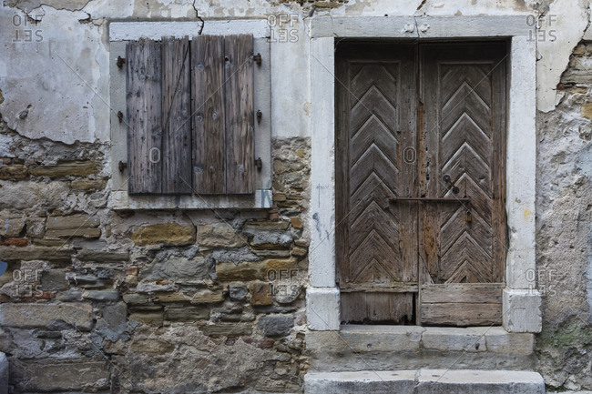 A view of a wooden door and shuttered window