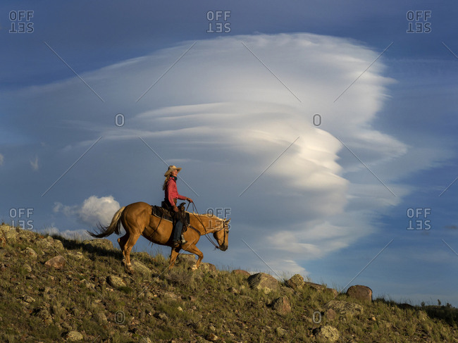 A female ranch wrangler riding horse in front of cloud