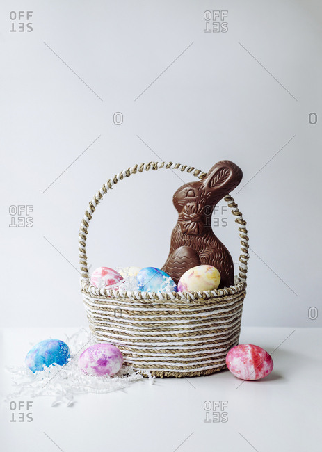 Painted Easter eggs in a natural basket with a chocolate bunny