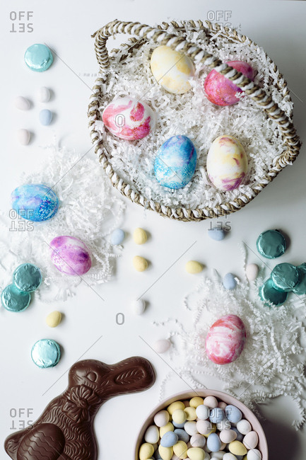 Top down view of painted Easter eggs in a natural basket with a chocolate bunny and other candy