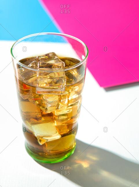 Glass bourbon iced tea on colorful studio backdrop