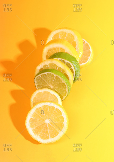 Lemon and lime citrus on yellow/orange background