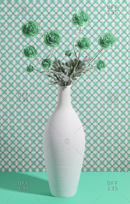 Artificial flowers in white vase arranged against patterned background