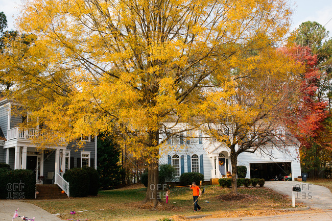 Father and daughter raking leaves on fall day