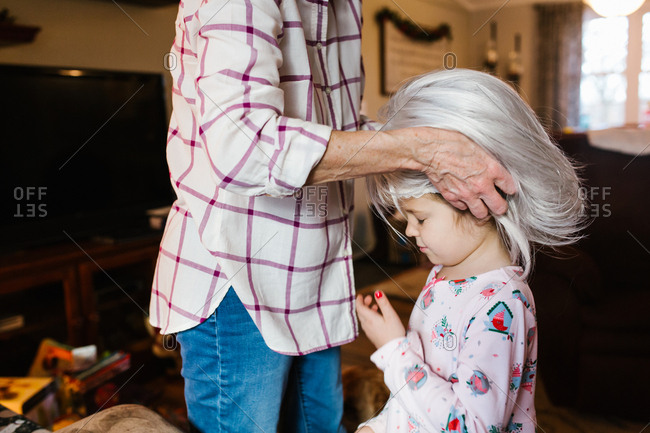 Grandmother putting wig on granddaughter for playtime
