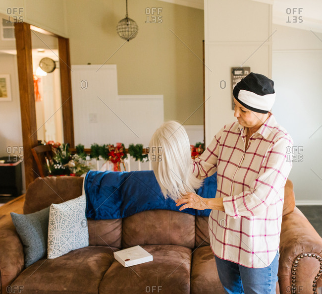 Radiation patient looking solemnly at wig in living room