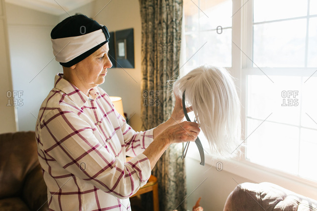 Female cancer survivor taking care of wig at home
