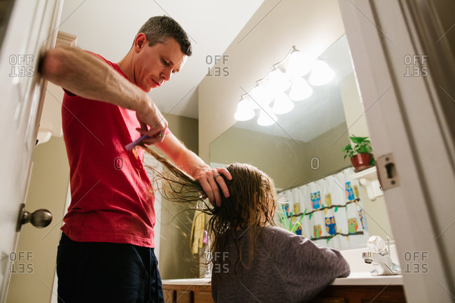 Father carefully brushing tangles out of daughter's wet hair