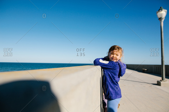 Girl squinting through bright sunlight on pier
