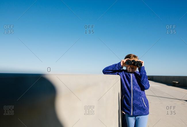 Little girl looking through binoculars on ocean pier