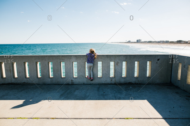 Back view of young girl enjoying ocean view from dock