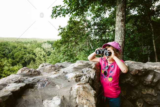 Curious child checking out forest view with binoculars