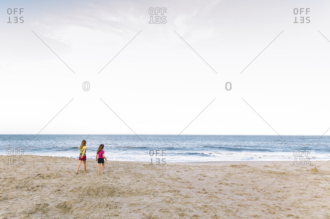 Sisters walking across beach to shore during summer break
