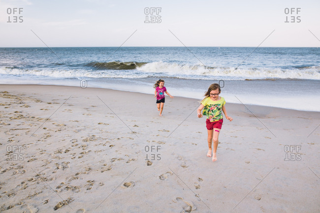 Laughing sisters running from fast waves on beach
