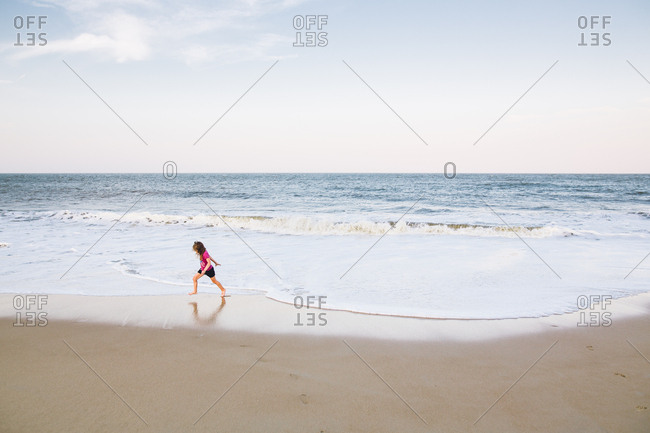 Girl playing by herself at the edge of the beach