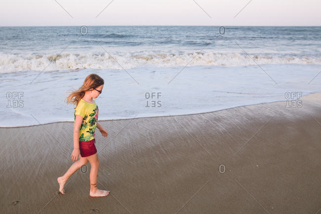 Girl with glasses walking barefoot in wet sand in front of tide