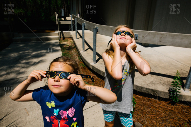 Sisters holding solar glasses close to their faces for the eclipse