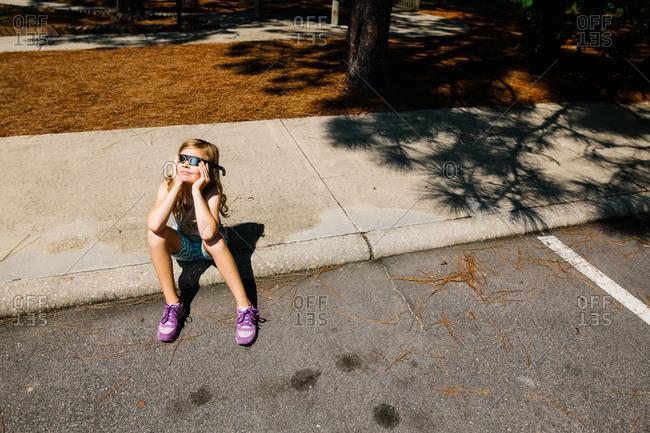 Girl waiting anxiously for solar eclipse on sidewalk curb