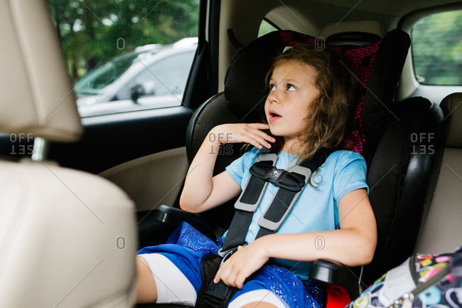 Preschooler  looking out car window in booster seat