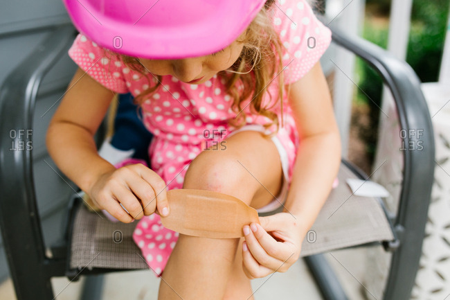 Brave girl tending to knee scrape with bandage