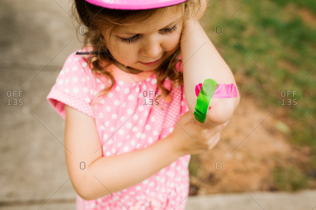 Preschooler showing off her colorful bandages on elbow injury