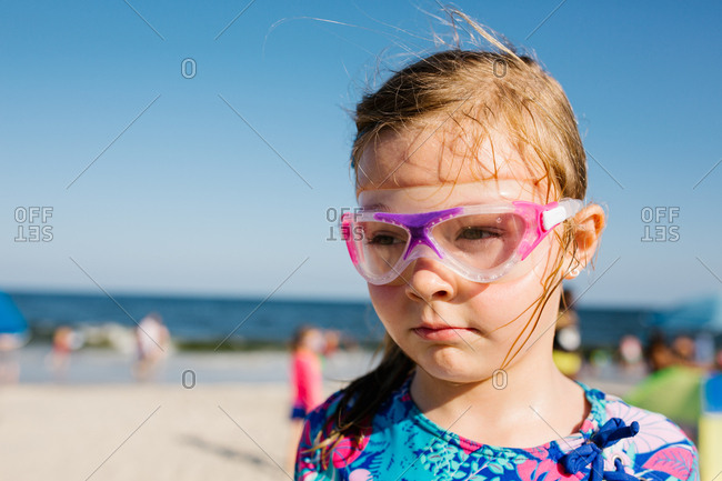 Serious faced little girl in goggles at the beach