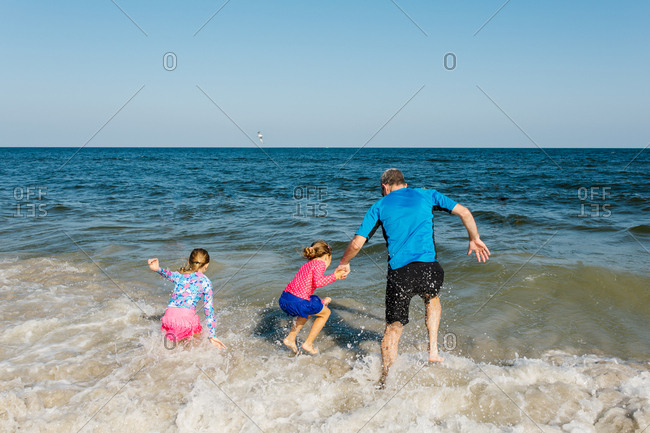 Father and daughters splashing around at the beach