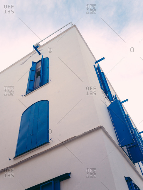 Looking up at the corner of a building with blue shutters against the sky