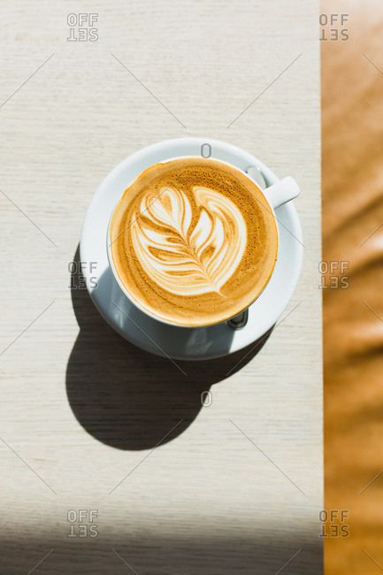 Overhead view of cappuccino decorated with fern leaf on edge of table