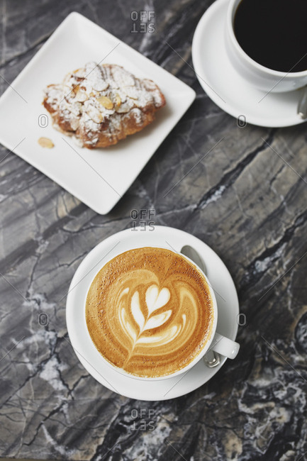 Overhead view of cappuccino decorated with fern leaf served with almond croissant