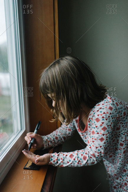 Girl wearing pajamas using a pen to write on her hand next to window