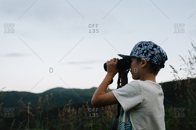 Boy using binoculars to look out at Alaskan wilderness landscape