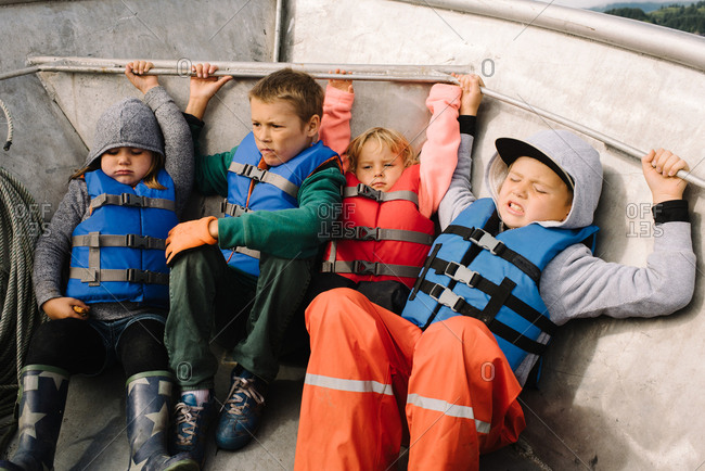 Children holding on to inside of fishing boat
